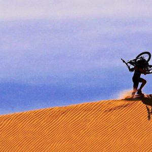 Portage du fatbike sur la crête d'une dune de sable